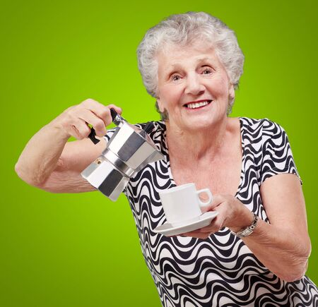 portrait of a vitality senior woman serving a tea cup over green background Stock Photo - 13280107