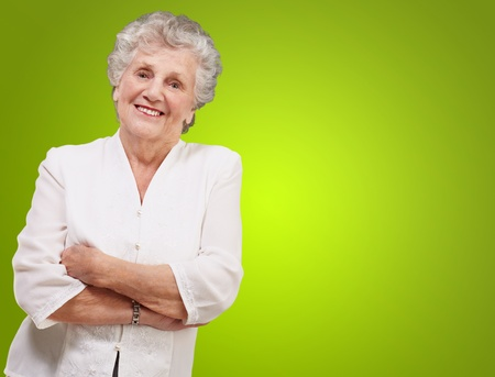 portrait of a adorable senior woman standing over green background Stock Photo - 13280385