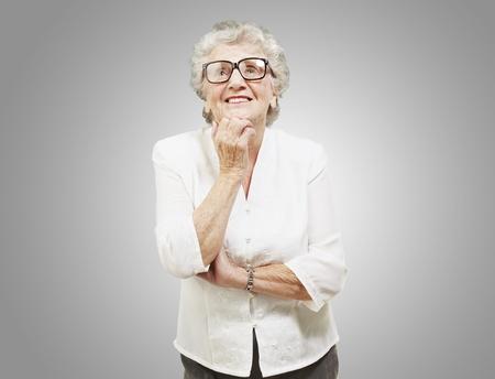 portret van senior vrouw denken en te kijken over grijze achtergrond Stockfoto