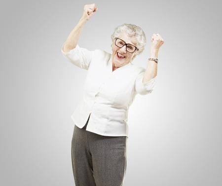 ritratto di una vittoria allegra anziano donna gesticolare su sfondo grigio