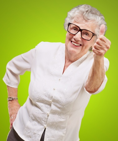 portrait of adorable senior woman doing good gesture over green photo