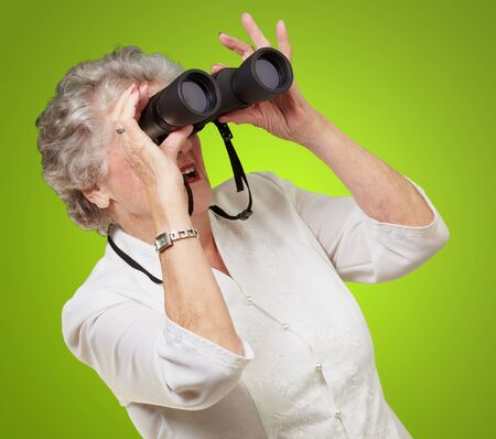 portrait of senior woman looking through a binoculars over green background Stock Photo - 13280072