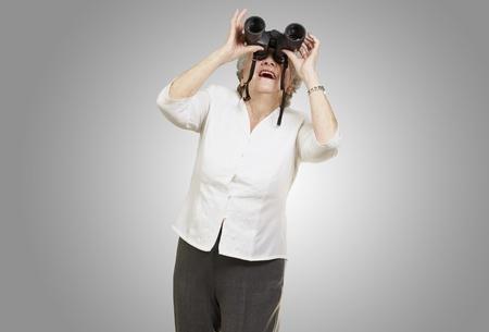 portrait of senior woman looking through a binoculars against a grey background photo