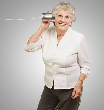 portrait of senior woman hearing with metal tin can over grey background photo