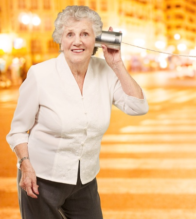 portrait of senior woman hearing with metal tin at night city Stock Photo - 13280499