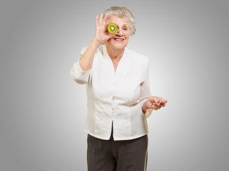 portrait of senior woman holding kiwi in front of her eye over grey background photo