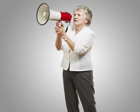 portrait of senior woman holding megaphone over grey background photo
