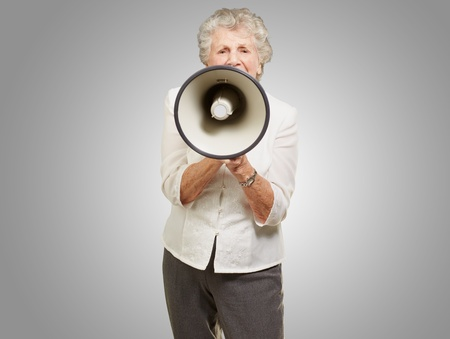 portrait of senior woman screaming with megaphone over grey background photo