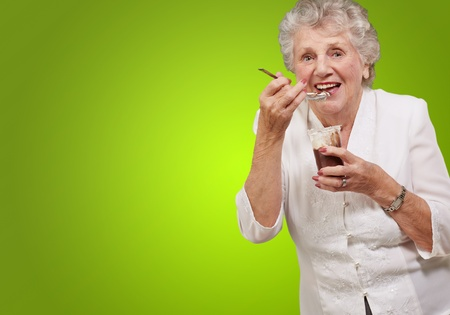 portrait of senior woman eating chocolate and cream cup over green photo