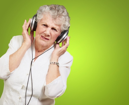 portrait of senior woman listening to music over green background photo