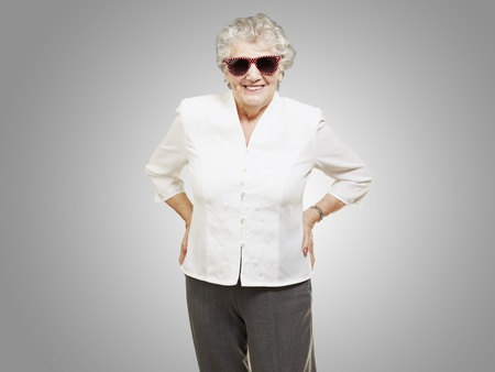 portrait of senior woman standing wearing sunglasses over grey background photo