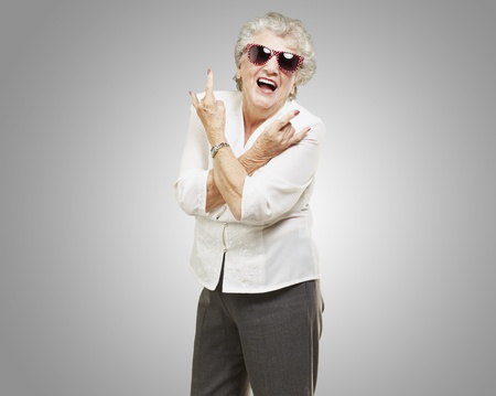 rocker: portrait of senior woman doing rock symbol over grey background Stock Photo