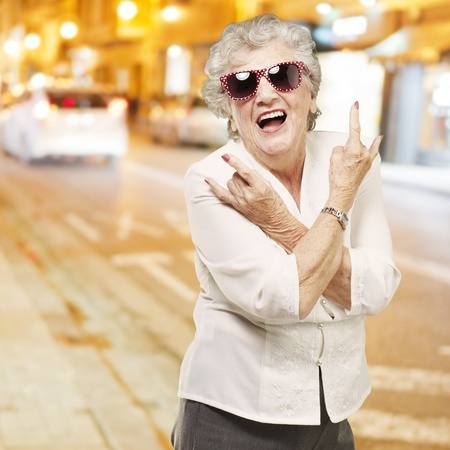 shades of grey: portrait of senior woman doing rock symbol against a city night Stock Photo