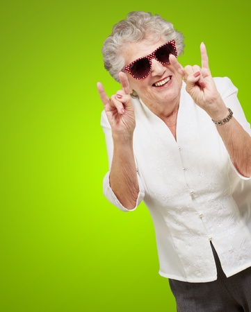 portrait of a happy senior woman doing rock symbol over green background Stock Photo - 13280092