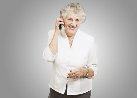 portrait of senior woman talking on mobile over grey background Stock Photo - 13280472