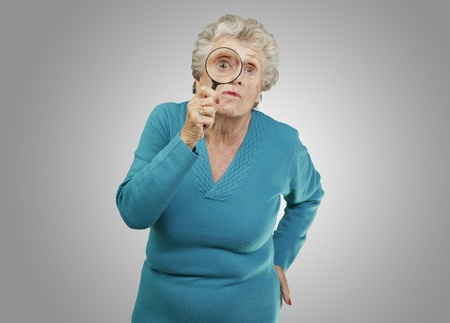 portrait of senior woman looking through a magnifying glass over grey background Stock Photo - 13280400