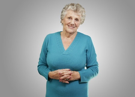portrait of senior woman standing over grey background photo