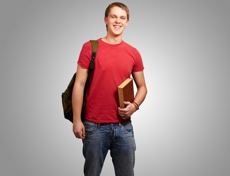 portrait of young student holding book and carrying backpack over grey photo