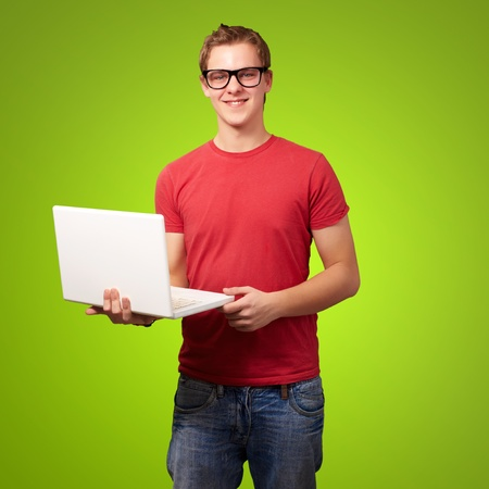 portrait of young student man holding laptop over green background photo