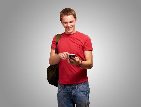 portrait of young man touching mobile screen over grey background photo