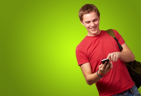portrait of young man touching mobile screen over green background photo