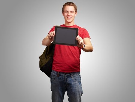 portrait of young man holding a digital tablet over grey background photo