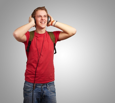 portrait of cheerful young student listening music with headphones over gery photo