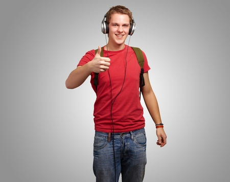portrait of cheerful young student listening music and gesturing good with headphones over grey photo