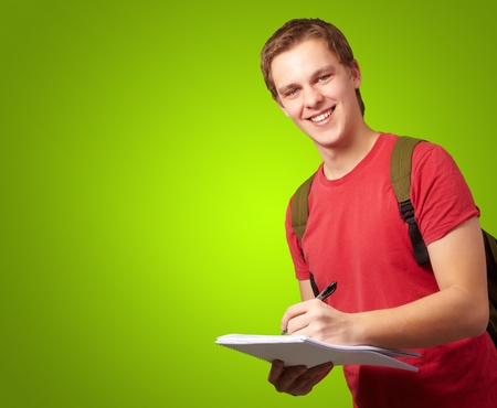 portrait of young student man writing on a notebook over green background photo