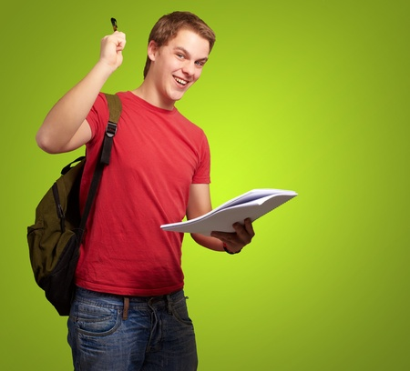 portrait of handsome student holding notebook and pen over green photo