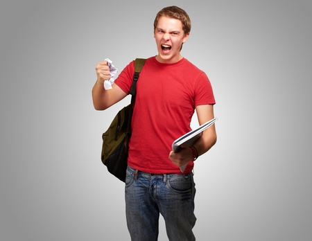 young angry student man roughing a sheet over grey background photo
