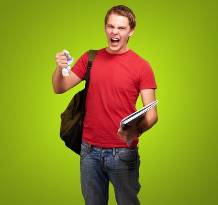 young angry student man roughing a sheet over green background photo