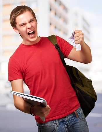 young angry student man roughing a sheet against a university Stock Photo - 13280551