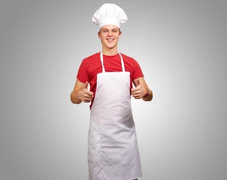 delantal: Retrato de hombre joven cocinero haciendo el s�mbolo de �xito sobre fondo gris Foto de archivo