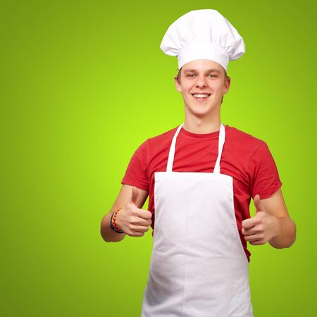 portrait of young cook man doing success symbol over green background photo