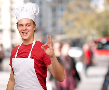 portrait of young cook man doing success symbol at crowded street Stock Photo - 13280075