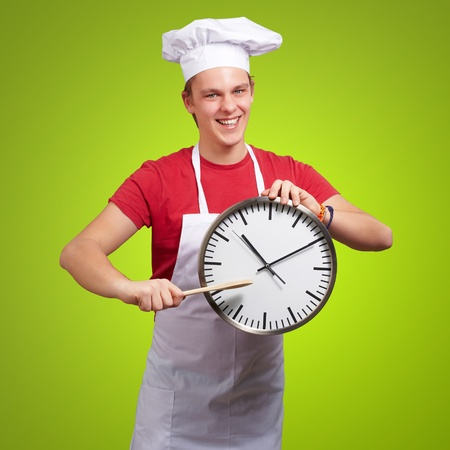 portrait of young cook man pointing a clock over green background photo