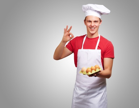 portrait of young cook man holding egg box and doing good gesture over grey photo