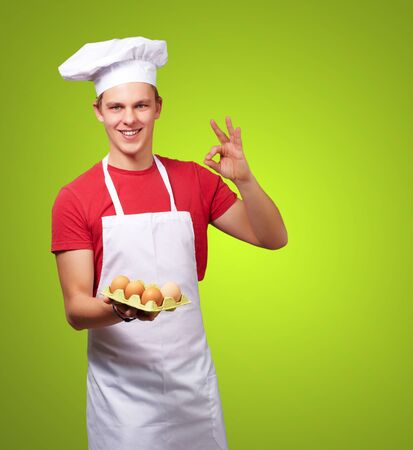 portrait of young cook man holding egg box and doing good gesture over green photo