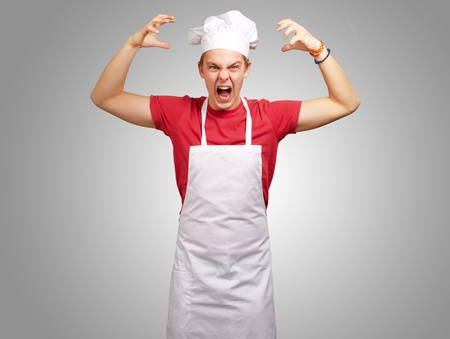 portrait of young cook man wearing apron doing aggressive gesture over grey photo