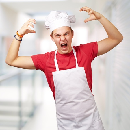 portrait of young cook man wearing apron doing aggressive gesture over abstract background photo