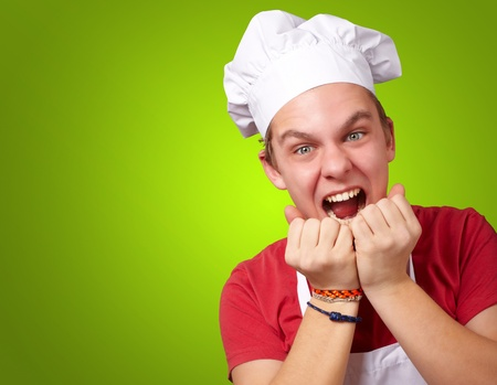 portrait of young cook man screaming over green background photo