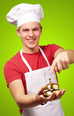 portrait of young cook man pressing a golden bell over green background photo
