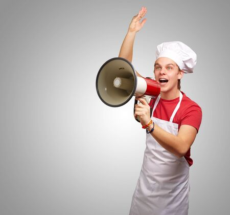 portrait of young cook man shouting with megaphone over grey background photo