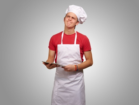 portrait of young cook man holding a digital tablet and thinking over grey background photo