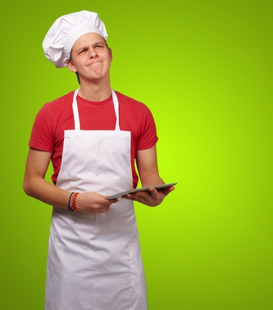 portrait of young cook man holding a digital tablet and thinking over green background photo