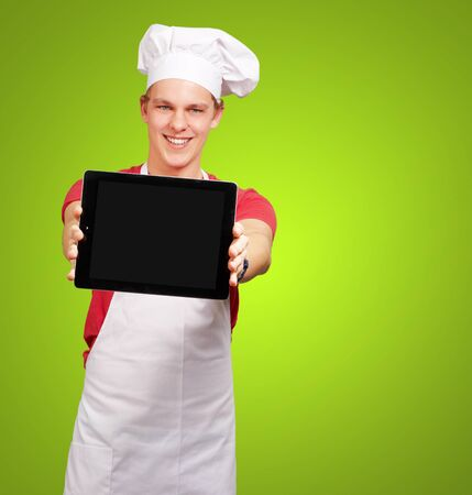 portrait of young cook man showing a digital tablet over green background photo