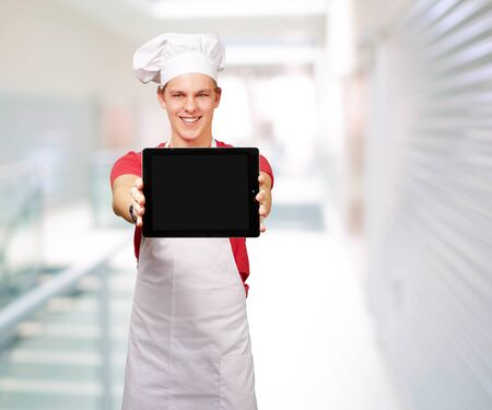portrait of young cook man showing a digital tablet at entrance of modern building photo