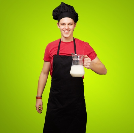 portrait of young cook man holding milk jar over green background photo