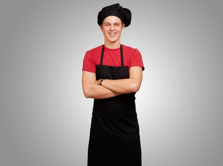 portrait of young cook man wearing uniform and smiling over grey background Stock Photo - 13280108